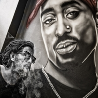 Man with locks walking in from of Tupac Shakur wall painting