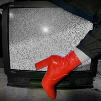 leg of woman with red boots sitting on TV