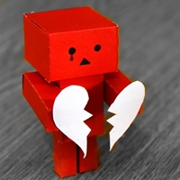 Red paper robot holding white broken heart