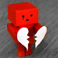 Red paper robot holding white broken heart